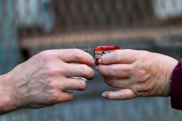 Two different people toasting to health and good harvesty in their lifes. hands of woman