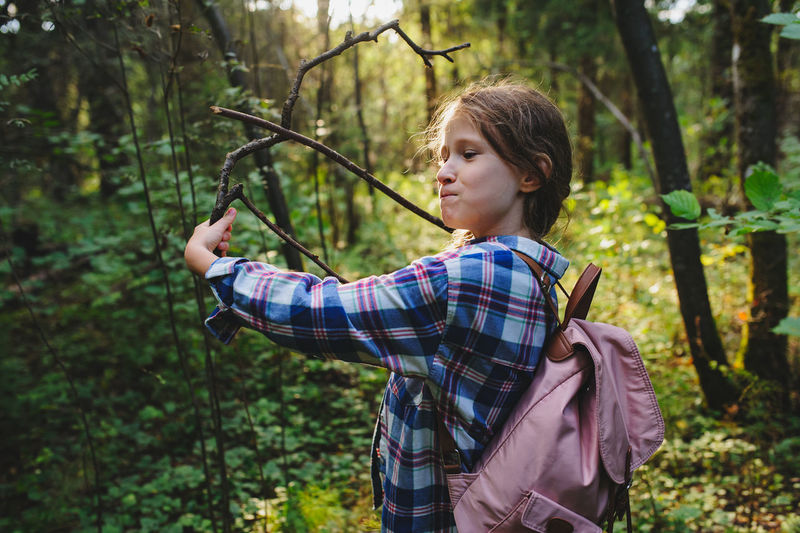 Side view of girl holding sticks at forest