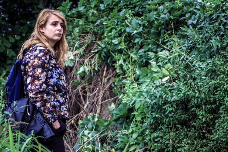 Side view of young woman looking away while standing against plants in forest