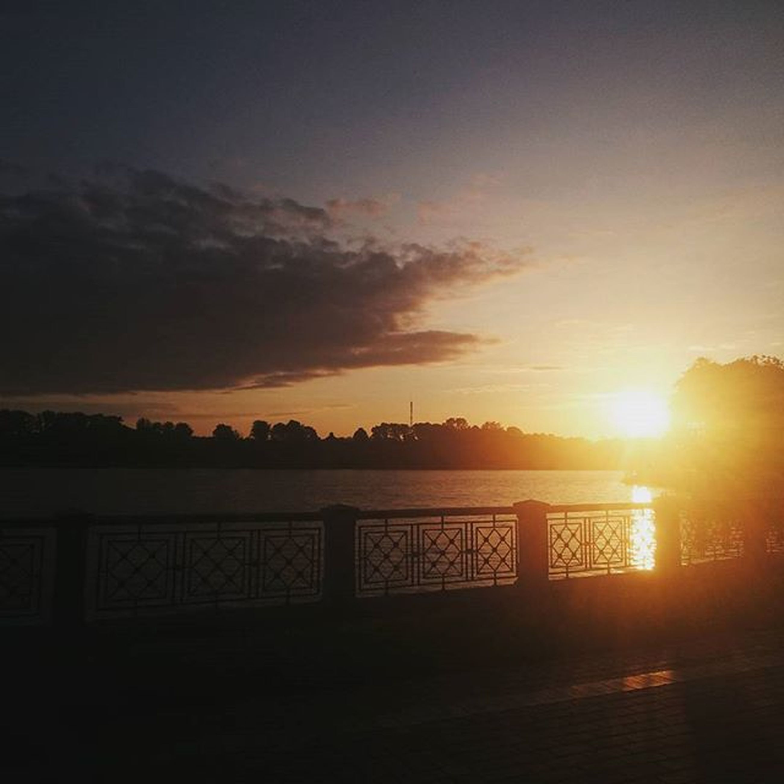 sunset, sun, silhouette, sky, orange color, built structure, railing, architecture, water, sunlight, scenics, tranquility, beauty in nature, tranquil scene, sunbeam, river, bridge - man made structure, cloud - sky, nature, connection