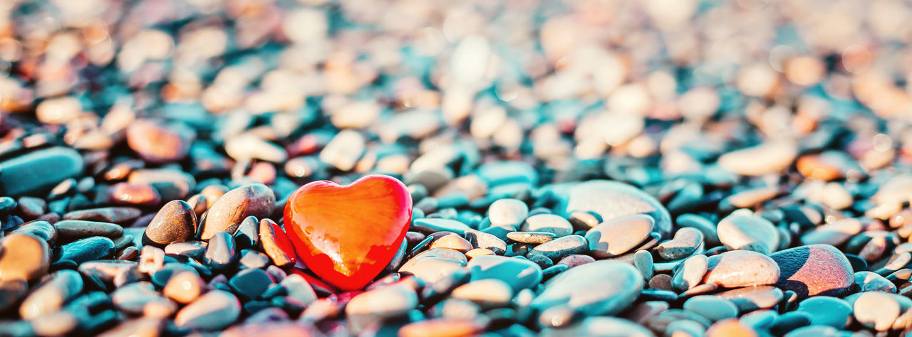 Close-up of heart shape stone on pebbles