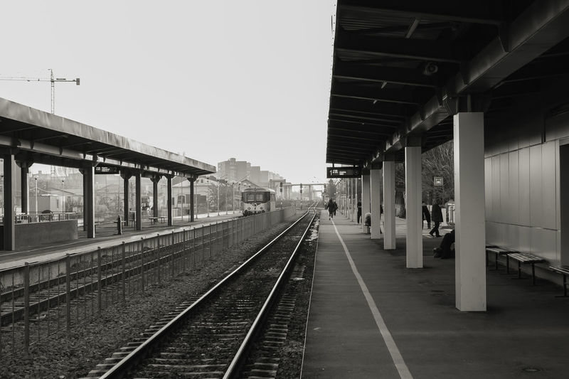Train StationArchitecture Black & White Built_Structure Clear Sky Cloud Cold Temperature Day Outdoors Public Transportation Rail Transportation Railroad Station Railroad Station Platform Railroad Track Sky Transportation Trip Old Train Station Solitude EyEmNewHere Woman Around The World Eyemphotography Citylife B&W Collection The Architect - 2017 EyeEm Awards Neighborhood Map Let's Go. Together. Been There. An Eye For Travel