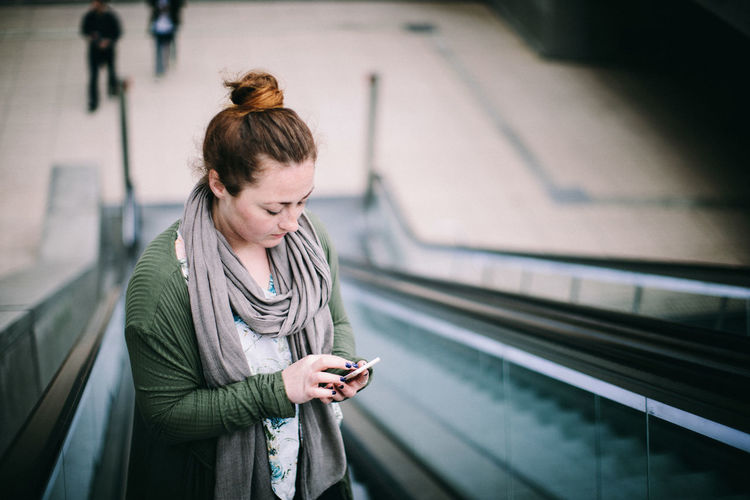 Young woman using mobile phone at railroad station