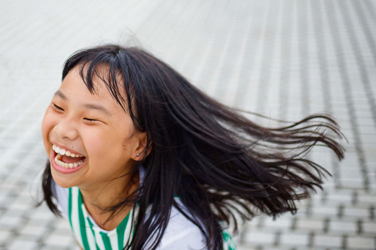 Happy asian little girl having fun at outdoor Asian Girl Black Hair Casual Clothing Cheerful Child Childhood Emotion Enjoyment Eyes Closed  Fun Hair Hair Toss Hairstyle Happiness Headshot Human Face Human Hair Innocence Long Hair One Person Outdoors Portrait Positive Emotion Smiling Tousled Hair 50 Ways Of Seeing: Gratitude Moments Of Happiness The Art Of Street Photography
