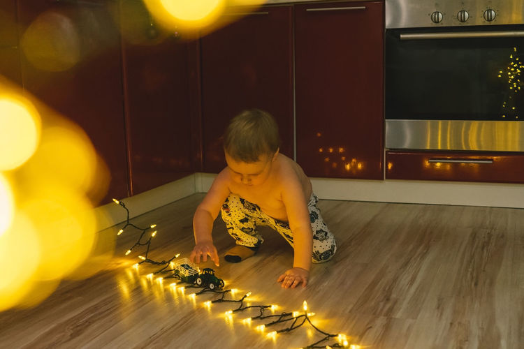 Full length of cute boy sitting by illuminated lights on floor