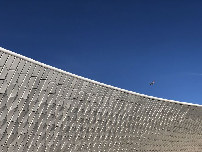Tiled exterior of MAAT museum in Belem, Lisbon, Portugal under a clear blue sky Lisbon Portugal Belém White Tiles Abstract Sky Architecture Built Structure Blue Clear Sky Day Nature Copy Space Flying Building Exterior No People Low Angle View Mid-air Outdoors Sunlight City Bird Sport Vertebrate Animal Themes