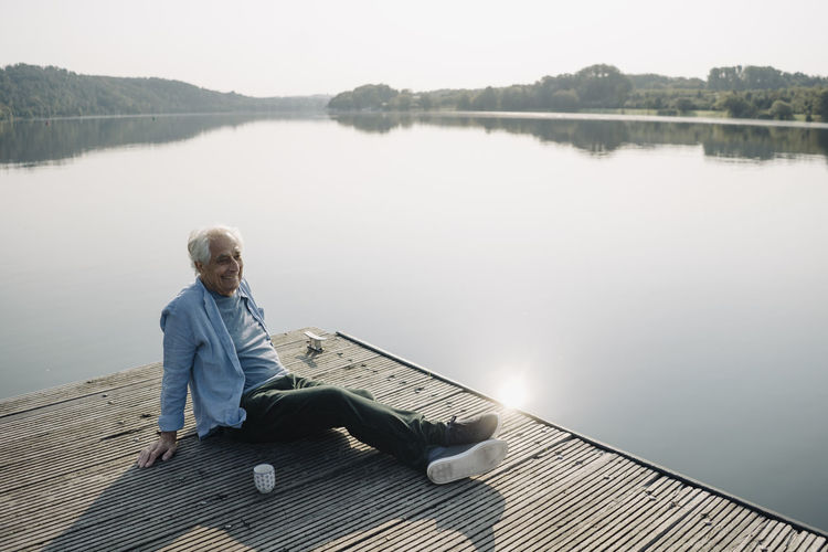 Man sitting on pier over lake