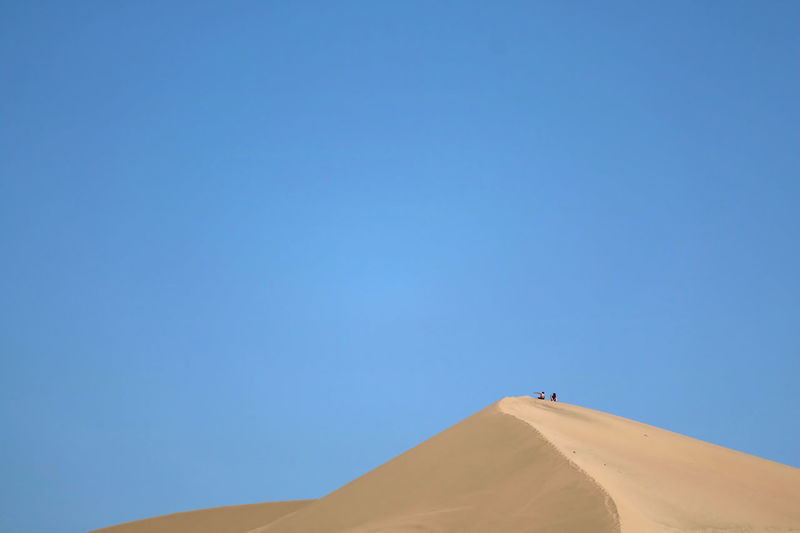 Low angle view of desert against clear blue sky