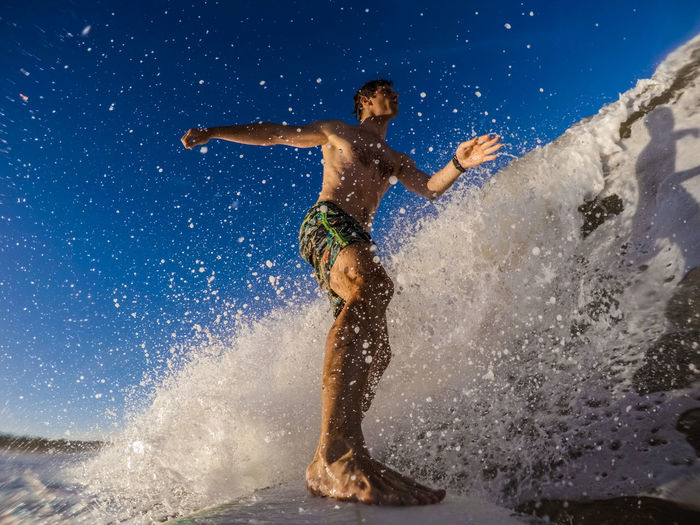Full length of man jumping on water