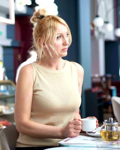 Thoughtful woman with coffee cup on table sitting in cafe
