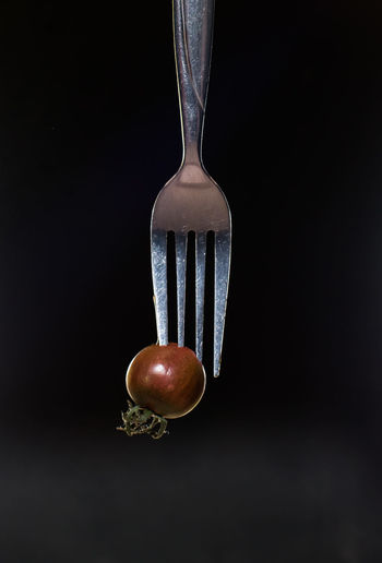 Small kumato tomato on fork isolated on the black background. Black Background Close-up Day Decor Food Food And Drink Freshness Healthy Eating Indoors  Kitchen Utensil Kitchen Utensils Kumato Tomato No People Photo For Kitchen Interior Ready-to-eat Restaurant Decor Restaurant Interior Design Studio Shot Tomato Vegetable
