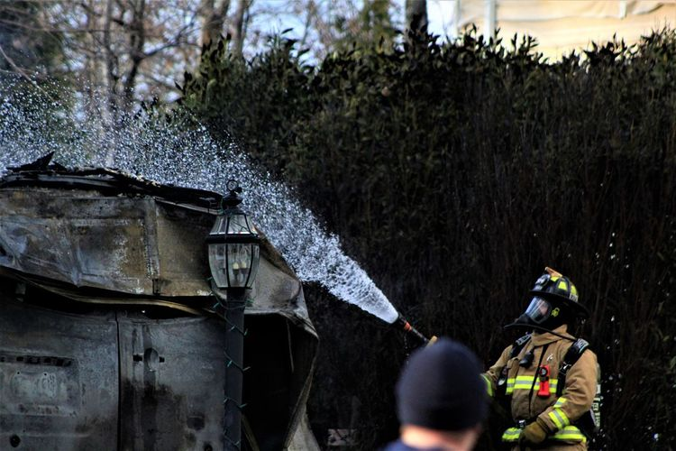 Firefighter spraying water on built structure
