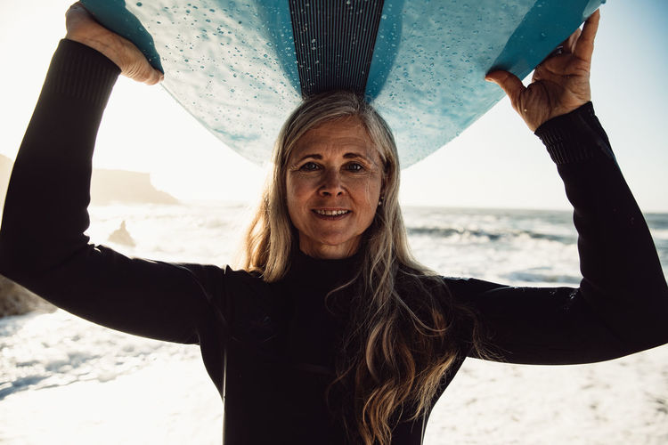 Portrait of woman carrying surfboard at beach