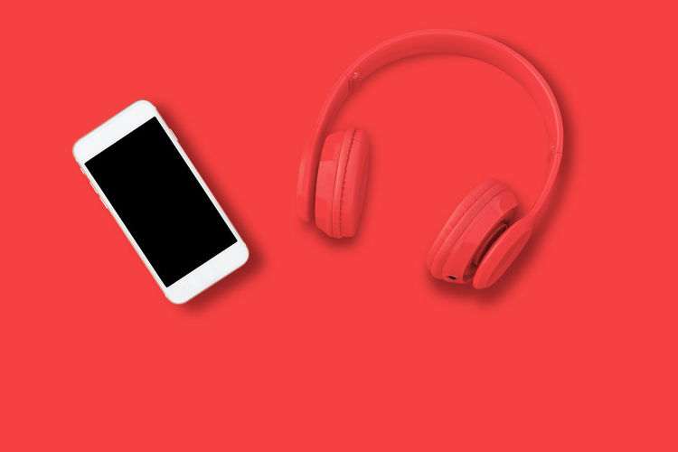 High angle view of smart phone over red background