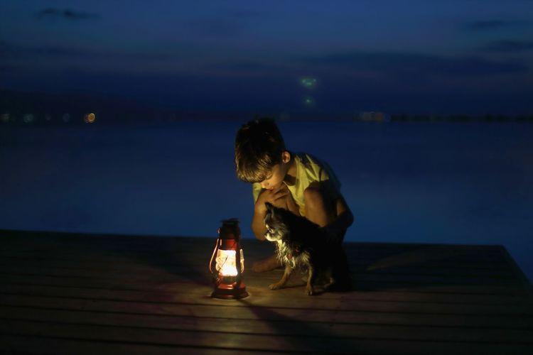 Woman sitting at illuminated shore against sky at night