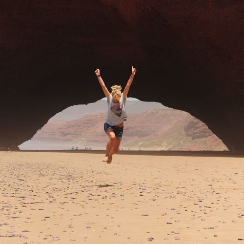 Full length of woman with arms outstretched against rock formation at sandy beach