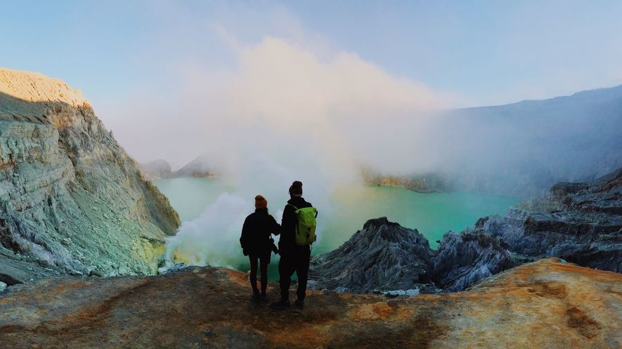 Rear View Of Man And Woman Hiking At Ijen