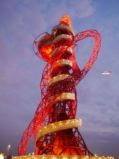 Olympic Park, London, 2012. The ArcelorMittal Orbit photographed on a cloudy night with blimp flying in background. EyeEmNewHere Traditional Festival Sky Outdoors Orbit No People Night Low Angle View Illuminated Celebration Carousel Blimp Arcelormittal Olympics Olympic London 2012 London Architecture AI Now