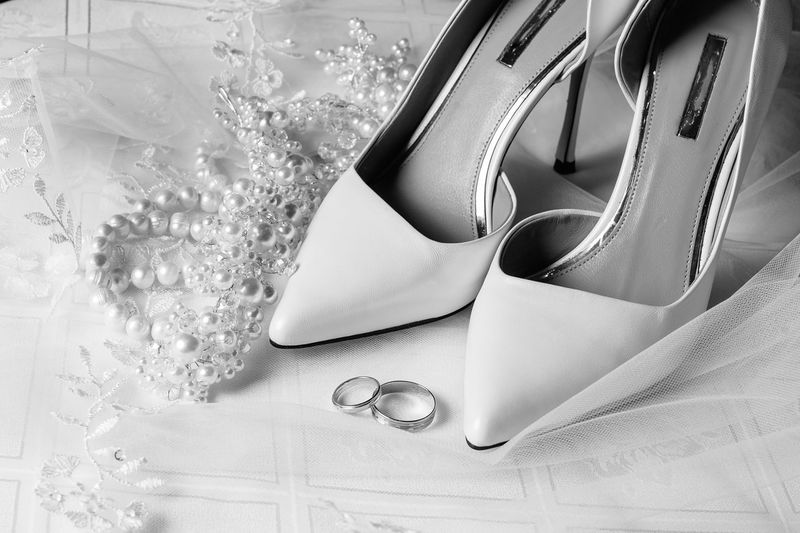 High angle view of wedding rings with shoes on table