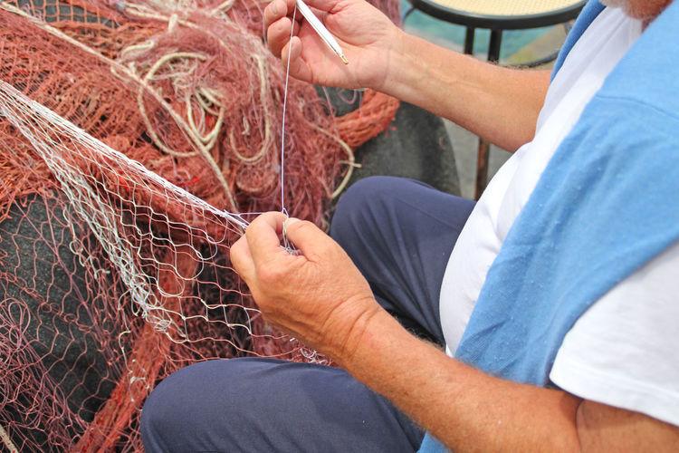 repairing fishing net At Work Close-up Day Fischernetz Fisherman Fishing Fishing Net Needle Person Repair Repairing Skill  Thread Unrecognizable Person