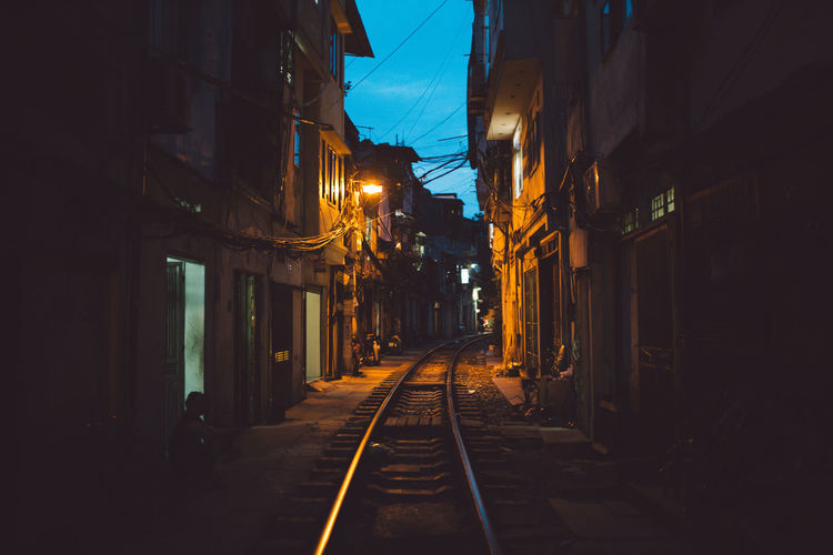 Railroad track amidst buildings against sky at night