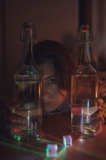 Portrait of woman with wine bottles at home