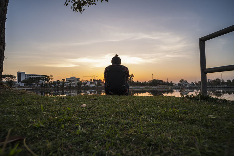Rear view of man sitting on field against sky during sunset