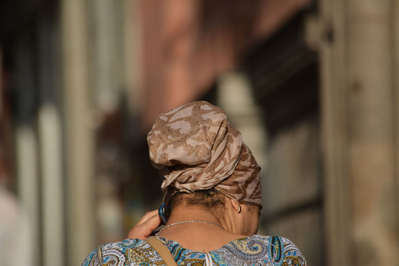 Rear view of woman head covered with scarf while using smart phone