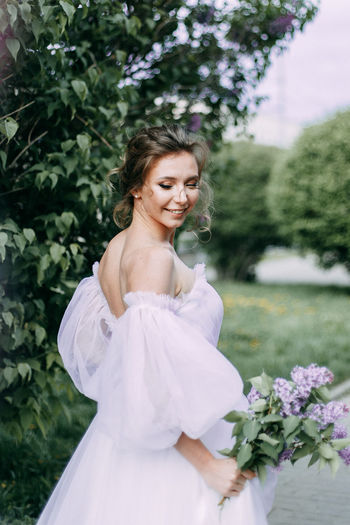 Beautiful bride in a wedding dress walks in a blooming apple-tree park in spring