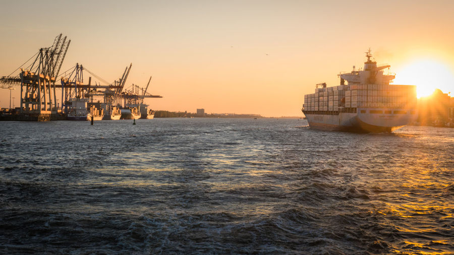 Enormous container ship leaving Hamburg harbor towards the open sea. Ship Transportation Nautical Vessel Water Sea Mode Of Transportation Sunset Waterfront Outdoors Freight Transportation River Vessel Container Ship Container Port