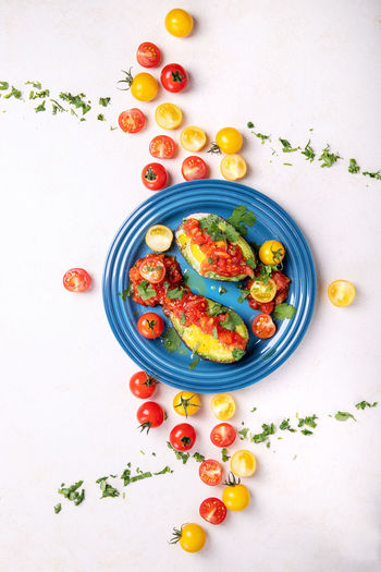 High angle view of egg in avocado with cherry tomatoes served in plate on table