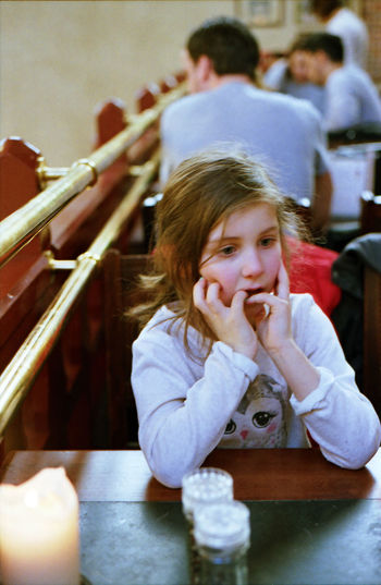 Thoughtful girl with fingers in mouth sitting in restaurant