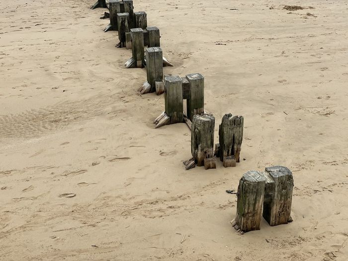 High angle view of wooden posts on beach