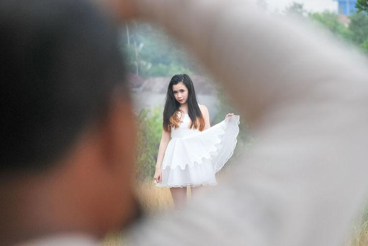 Young Woman Wearing White Dress Seen Through Man Arm