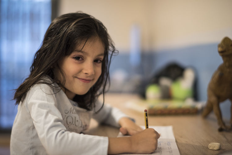 Portrait of smiling girl writing in book on table