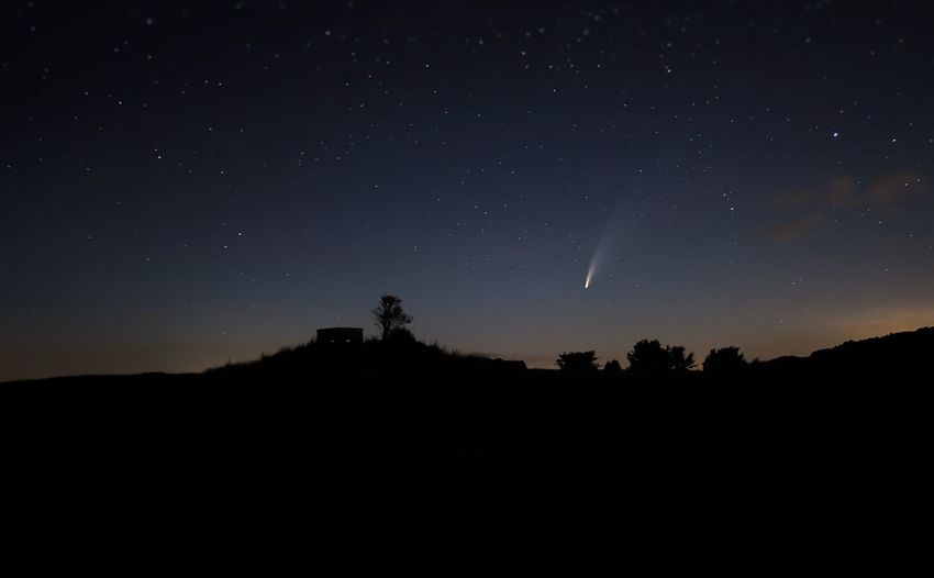 Silhouette landscape against sky at night with meteor