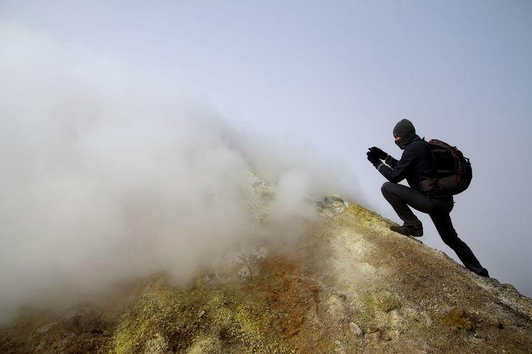 Man climbing mt etna against sky
