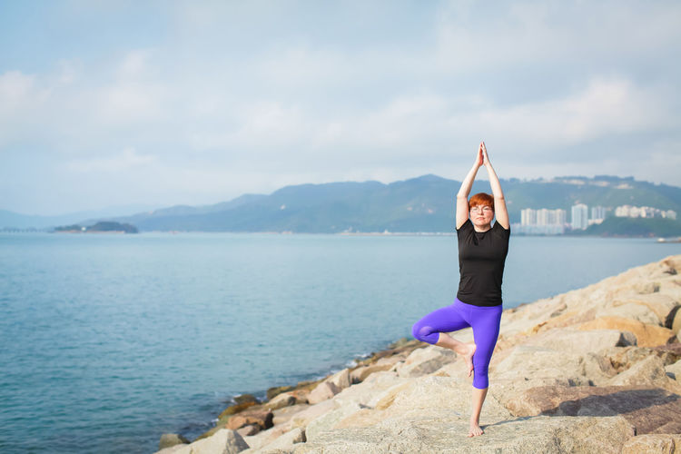Full length of woman practicing yoga on rock by sea against sky