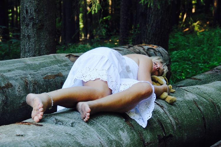 Woman sleeping on logs at forest