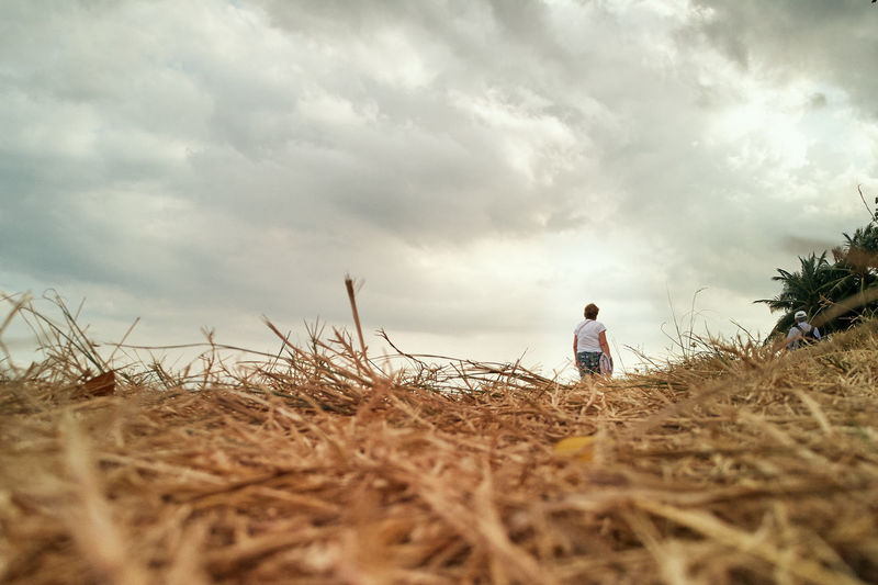 Cloud - Sky Sky Plant Land One Person Nature Field Real People Beauty In Nature Leisure Activity Tranquility Day Selective Focus Lifestyles Outdoors Standing Child Agriculture Grass Dry