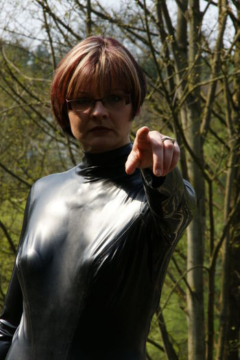 Portrait of woman gesturing while standing against tree
