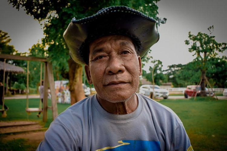 Portrait of senior man wearing hat sitting at park