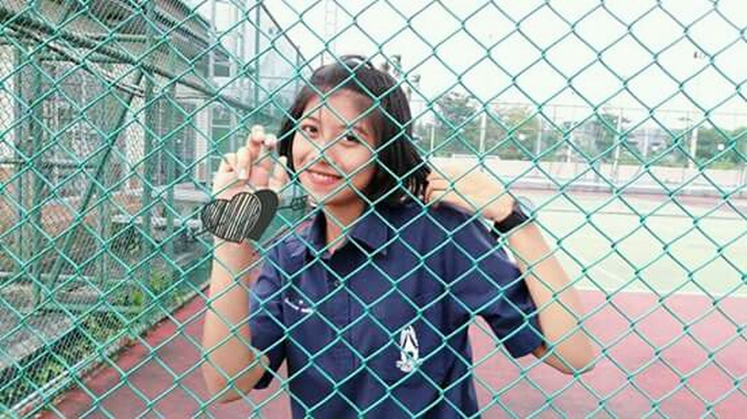 chainlink fence, fence, disappointment, one person, leaning, youth culture, teenager, people, grid, sport, front view, black hair, outdoors, wire mesh, introspection, young women, young adult, sports clothing, adult, day, adults only