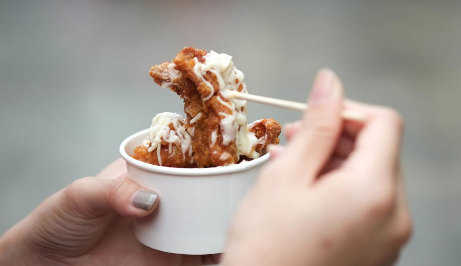 Close-up of woman hand holding fried chicken in cup
