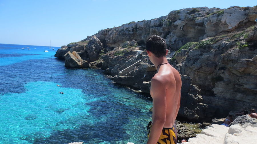 Shirtless man standing on rock by sea against clear sky