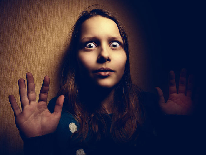 Portrait of shocked woman against wall at home