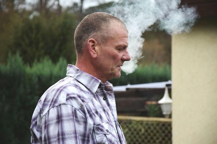Close-up of man exhaling smoke outdoors