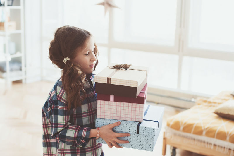 happy kid girl preparing or getting many gifts for birthday. Child with stack of gifts at home One Person Indoors  Real People Holding Casual Clothing Child Lifestyles Childhood Girls Box Gift Gift Box Holiday Birthday Surprise New Year Christmas Celebrating