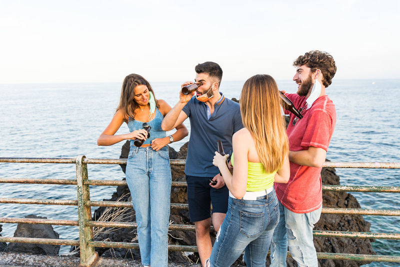 Friends drinking beer while standing by railing against sea