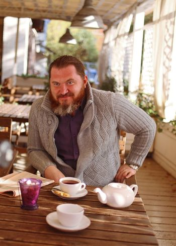 Looking At Camera Table Sitting Food And Drink Adult One Person Facial Hair Men Portrait Smiling Cup Drink Beard Casual Clothing Indoors  Males  Mug Lifestyles Mid Adult Crockery Hot Drink Breakfast Tea Cup